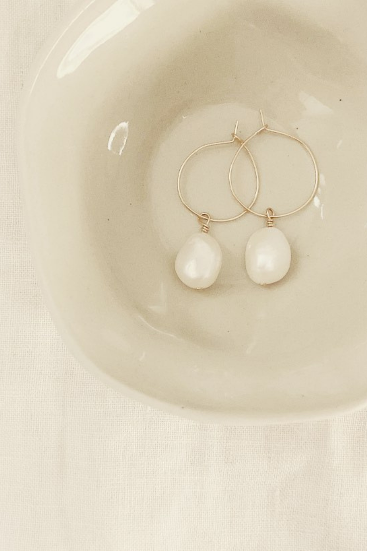 Hoop earrings made with sterling silver, 14k yellow gold or rose gold, and a single baroque freshwater pearl, natural (white) in colour. Freshwater pearls are natural and have a raw organic finish, their shape is unique and imperfections are common.